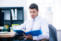 Businessman sitting at the table and reading document Stock Photography