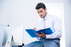 Businessman sitting on the table and reading document Royalty Free Stock Photos