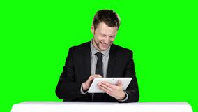 Businessman sitting at the table and uses laptop. Green screen stock video