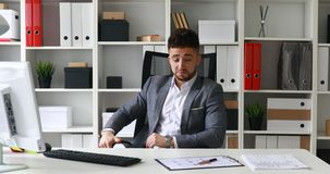 Businessman sitting at table in white office and throwing hands behind head swaying in office-chair.