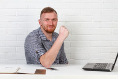 Businessman sitting at the table and working on the computer. It solves important business tasks. He is successful and well-traine Royalty Free Stock Photos