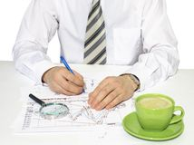 Businessman sitting at a table and writes Royalty Free Stock Photos