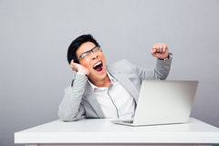 Businessman sitting at the table and yawning Stock Photos
