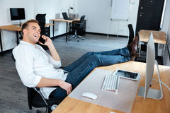 Businessman sitting and talking on cell phone in office Royalty Free Stock Photography