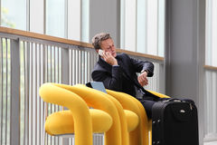 Businessman sitting talking on the phone, on a business travel stock photography