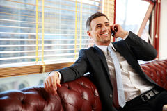 Businessman sitting and talking on the phone. Happy businessman sitting and talking on the phone at office Royalty Free Stock Images