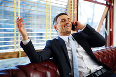 Businessman sitting and talking on the phone Stock Photos