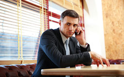 Businessman sitting and talking on the phone Stock Images