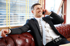 Businessman sitting and talking on the phone Stock Image