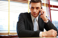 Businessman sitting and talking on the phone Stock Photo