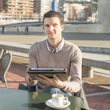 Businessman sitting on terrace bar with coffee cup and laptop ta Royalty Free Stock Photography