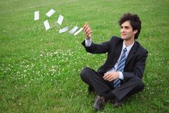 Businessman sitting and throwing paper cards Royalty Free Stock Photography