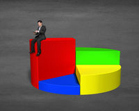 Businessman sitting on top of 3d pie chart. On concrete ground Stock Photo