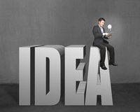 Businessman sitting on the top of 3D word IDEA with tablet and lighting bulb. In concrete wall background Royalty Free Stock Photos