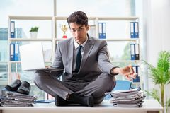 The businessman sitting on top of desk in office Stock Photography