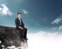 Businessman sitting on the top of a high mountain Royalty Free Stock Photos
