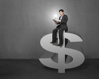 Businessman sitting on the top of money symbol with tablet and l. Ighting bulb in concrete wall background Stock Photo