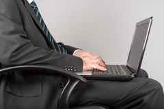 Businessman sitting and typing on his laptop Royalty Free Stock Photography