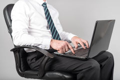 Businessman sitting and typing on his laptop Stock Photos