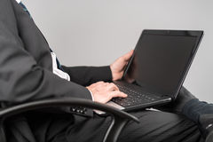 Businessman sitting and typing on his laptop Stock Photo