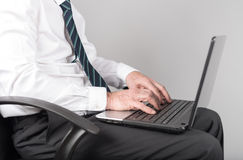 Businessman sitting and typing on his laptop Stock Photography