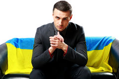 Businessman sitting with ukrainian flag Royalty Free Stock Images