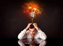 Businessman sitting under a blowing idea bulb Stock Photos