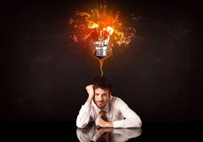 Businessman sitting under a blowing idea bulb Royalty Free Stock Photos