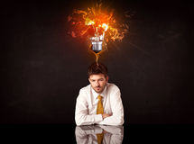 Businessman sitting under a blowing idea bulb Royalty Free Stock Images