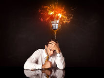 Businessman sitting under a blowing idea bulb Royalty Free Stock Image