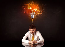 Businessman sitting under a blowing idea bulb Stock Photos