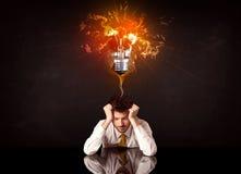 Businessman sitting under a blowing idea bulb Stock Photo