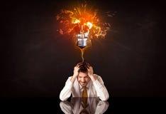 Businessman sitting under a blowing idea bulb Stock Image