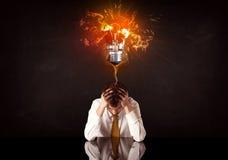 Businessman sitting under a blowing idea bulb Royalty Free Stock Photo