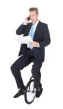 Businessman Sitting On Unicycle Talking On Cellphone Royalty Free Stock Photos
