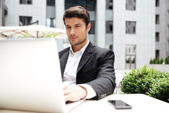 Businessman sitting and using laptop in outdoor cafe Royalty Free Stock Image
