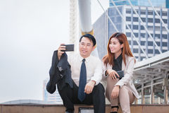Businessman sitting and using phone to take photo as selfie with Stock Photo