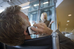 Businessman sitting in waiting area, using mobile phone, low angle view, rear view Royalty Free Stock Photo