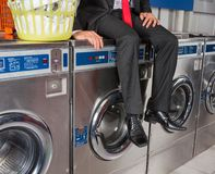 Businessman Sitting On Washing Machine Stock Photo