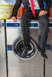 Businessman Sitting On Washing Machine Royalty Free Stock Photography