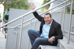 Businessman sitting and waving Royalty Free Stock Photo