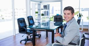 Businessman sitting on wheelchair in office. Portrait of smiling businessman sitting on wheelchair in conference room Royalty Free Stock Photo