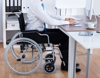 Businessman Sitting On Wheelchair And Using Computer stock photos