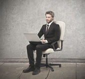 Man sitting on a white armchair Stock Photo