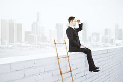 Businessman sitting on white brick wall and wooden ladder at cit Stock Images