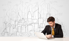 Businessman sitting at the white table with hand drawn buildings Stock Photography
