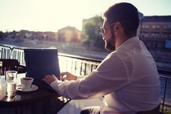 Businessman Sitting and Working on Laptop at Cafe Royalty Free Stock Image