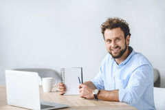 Businessman sitting at workplace with laptop and pointing at blank notebook in hand. Smiling businessman sitting at workplace with laptop and pointing at blank Royalty Free Stock Photo