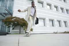 Businessman on skateboard Royalty Free Stock Image