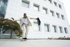 Businessman on skateboard Stock Image